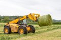 Loader Tractor Moving A Round Bale From Field Royalty Free Stock Photography - 72568867