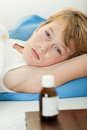Sick Boy Laying Down Next To Medicine Bottle Royalty Free Stock Images - 72675909