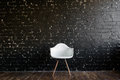 White Chair Standing In Room On Brown Wooden Floor Over Black Brick Wall Royalty Free Stock Images - 72711449