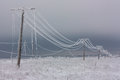 Broken Phase Electrical Power Lines With Hoarfrost On The Wooden Electric Poles On Countryside In The Winter After Storm Stock Photo - 72782340