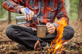 Man Traveler Pours Water From A Bottle Into A Metal Mug. Stock Photo - 72786490