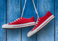 Red Sneakers Hanging On A Wooden Blue Background Royalty Free Stock Photo - 72856315