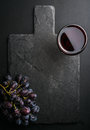 Glass Of Red Wine And Grapes On Black Slate Stone Board Over Dark Background Stock Photos - 72934003