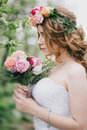 Beautiful Bride In A Wedding Dress With Bouquet And Roses Wreath Posing In A Green Garden Royalty Free Stock Photo - 73208225