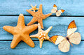 Starfish And Butterfly On The Blue Wooden Background. Summer Concept. Stock Images - 73211264