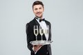 Cheerful Butler In Tuxedo Smiling And Offering Champagne Royalty Free Stock Images - 73266729