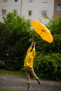 Little Fellow In A Bright Yellow Raincoat Flies Over The Earth With An Umbrella In Hand. Royalty Free Stock Image - 73313786
