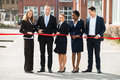 Businesspeople Cutting Ribbon Royalty Free Stock Image - 73411676