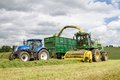 Harvester Forager Cutting Field, Loading Silage Into A Tractor Trailer Stock Photography - 73578322