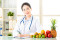 Young Asian Nutritionist Doctor Writing Diet Plan Royalty Free Stock Photo - 73671595