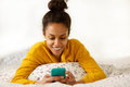 Smiling Young Woman Sitting In Bed With Mobile Phone Stock Images - 73921294