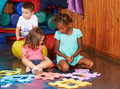 Children Playing With Jigsaw Puzzle In Kindergarten Royalty Free Stock Photography - 74144527