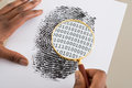 Using Magnifying Glass To Check Binary Code Within Finger Print Royalty Free Stock Photo - 74155105