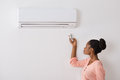 Woman Operating Air Conditioner With Remote Control Royalty Free Stock Photography - 74155287