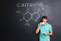 Man Drinking Coffee Over Blackboard With Structure Of Caffeine Molecule Royalty Free Stock Photo - 74177565