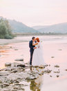 Attractive Young Wedding Couple Kissing. Shore Of A Mountain River With Stones On Background Royalty Free Stock Images - 74184859