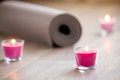 Lighted Pink Candle And Rolled Brown Yoga, Pilates Mat On The Fl Stock Photos - 74188073