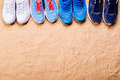 Various Sports Shoes In A Row Against Sand, Studio Shot Royalty Free Stock Photography - 74201187
