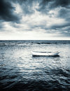 White Wooden Fishing Boat Under Stormy Clouds Royalty Free Stock Photo - 74242755