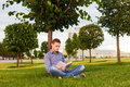 Student Reading Book Sitting In The Park Under Tree On The Grass Stock Images - 74305374