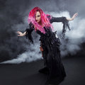 Halloween Witch Creates Magic. Attractive Woman With Red Hair In Witches Costume Royalty Free Stock Image - 74349906