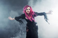 Halloween Witch Creates Magic. Attractive Woman With Red Hair In Witches Costume Standing Outstretched Arms, Strong Wind Royalty Free Stock Images - 74350039