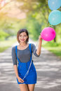 The Girl With Balloons Plays On The Road Royalty Free Stock Image - 74445636