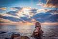 Sunrise Over A Rocky Beach. Colorful Clouds Reflecting In The Sea Stock Image - 74448871