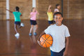 Boy Standing With Ball In Basketball Court Stock Photo - 74509930