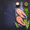 Two Raw Steak To Salmon, Seafood, Healthy Food With Herbs, Parsley, Olive Oil And Salt  Dark Vintage Cutting Board On Wooden Rus Royalty Free Stock Photo - 74515325