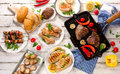Mixed Grilled Meats With Vegetables On A White Wooden Table. Stock Photography - 74629612
