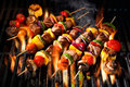Meat Kebabs With Vegetables On Flaming Grill Stock Photos - 74654163