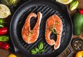 Dinner Cooking Ingredients. Two Pieces Of Raw Uncooked Salmon With Vegetables, Herbs, Lemon, Avocado, Artichokes, Spices Stock Image - 74665941