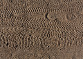Abstract Pattern Of Foot Prints And Bike Tyre Tracks On Sand. Royalty Free Stock Image - 74698936