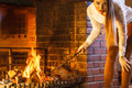 Woman With Fire Iron Poker At Home Fireplace. Stock Images - 74739224