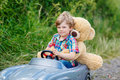 Little Kid Boy Driving Big Toy Car With A Bear, Outdoors. Royalty Free Stock Photo - 74858465
