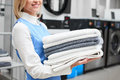 Worker Laundry Girl Holding Fresh Towels In Her Hands And Smiles Stock Images - 75023424
