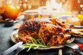 Thanksgiving Day Dinner Table Setting With Whole Roasted Turkey Or Chicken On Plate With Cutlery , Festive Lighting And Decoration Royalty Free Stock Photography - 75037457