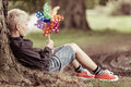 Blond Boy Holding Colorful Whirligig Sits By Tree Stock Photo - 75102790