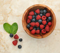 Raspberries And Blueberries In A Wooden Bowl Stock Image - 75182571