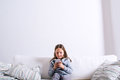 Little Girl Sitting On Sofa, Playing With Smartphone Stock Photography - 75251892