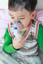 Asian Child Holds A Mask Vapor Inhaler For Treatment Of Asthma. Stock Photo - 75279160