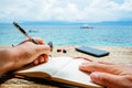 Caucasian Man Is Writing Sime Idea, Message Or Letter In His Notepad By Pen While He Sitting On The Beach Of Tropical Royalty Free Stock Images - 75281059