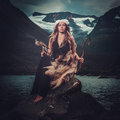 Nordic Goddess In Ritual Garment With Hawk Near Wild Mountain Lake In Innerdalen Valley. Stock Images - 75330394