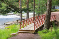 Small Wooden Bridge With Red Railings Over Stream Royalty Free Stock Image - 75390246