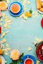 Cups Of Tea, Pot , Cakes And Flowers Petals On Light Blue Background Stock Image - 75403381