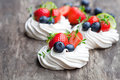 Mini  Pavlova Meringue Cakes  With Berries And Lime On Rustic Woo Stock Photo - 75421880
