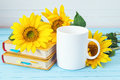 White Coffee Cup With Sunflowers And Yellow Books On Blue Wooden Stock Images - 75441964