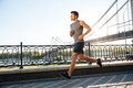 Side View Of Sportsman Running Along Bridge At Sunset Light Royalty Free Stock Photo - 75491285