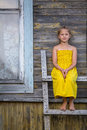 Little  Girl Sitting On A Wooden Ladder Near A Village House. Stock Image - 75509901